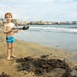 Kind mit Schaufel am Strand