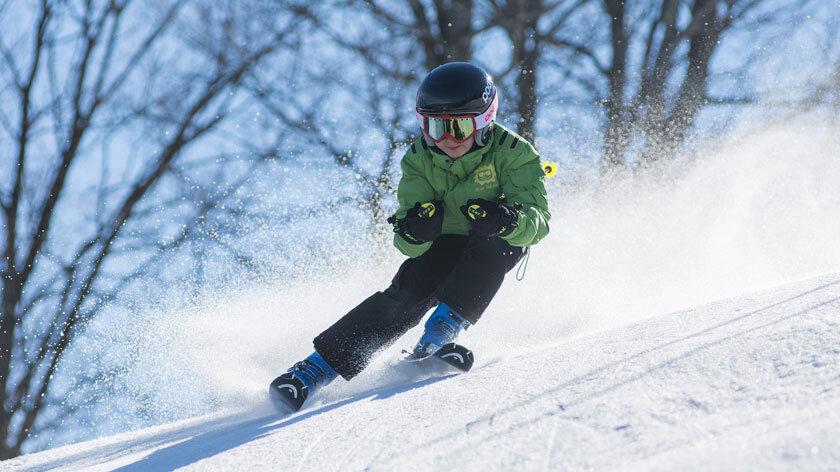 Junge bei Schussfahrt im Schnee