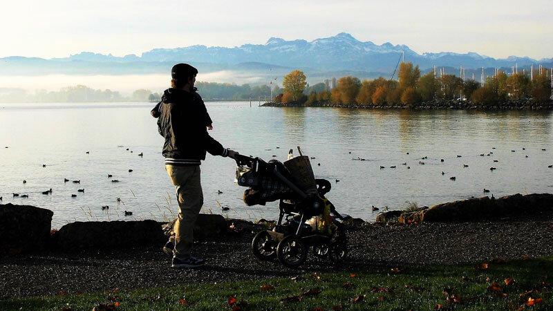 Vater am See mit Kinderwagen